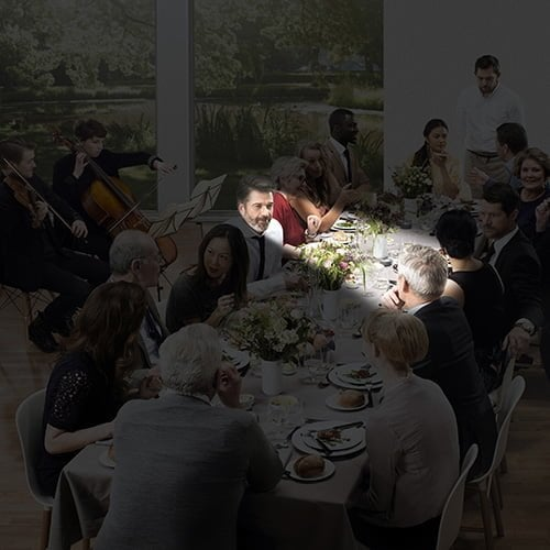 darkened image of people sitting in a dining room with a small section in light representing focused hearing