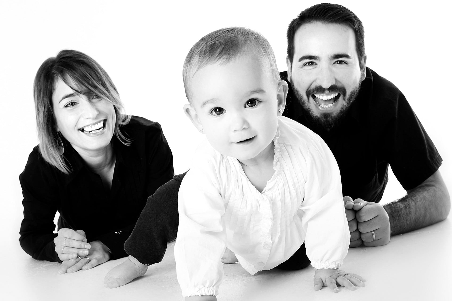 black and white image of family laying on the floor smiling with the parents behind the infant