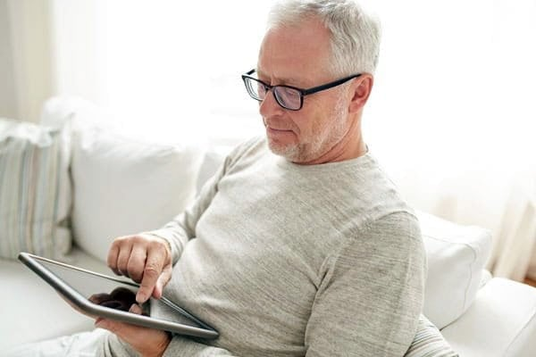 elderly man sitting on a couch reading and navigating a tablet